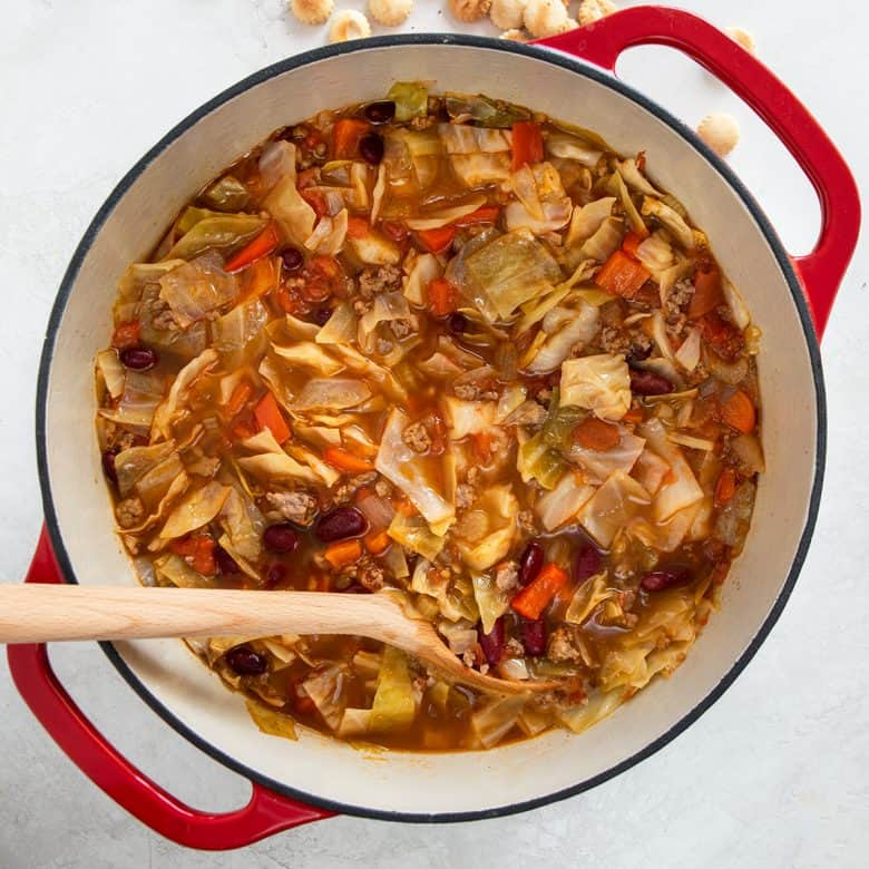 Overhead of Cabbage soup in a red Dutch oven with a wooden ladle in the soup.