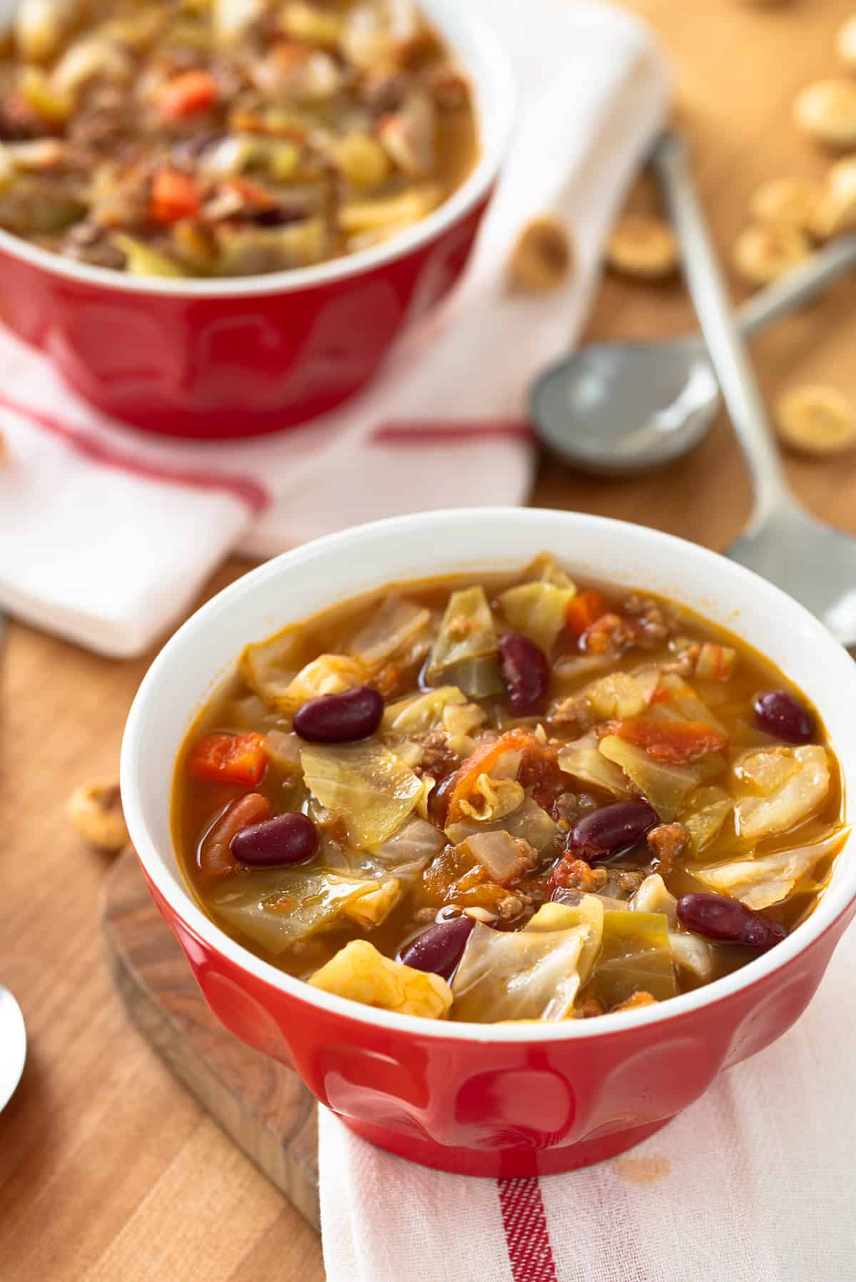Cabbage Beef Soup in a red bowl on wood top with crackers.