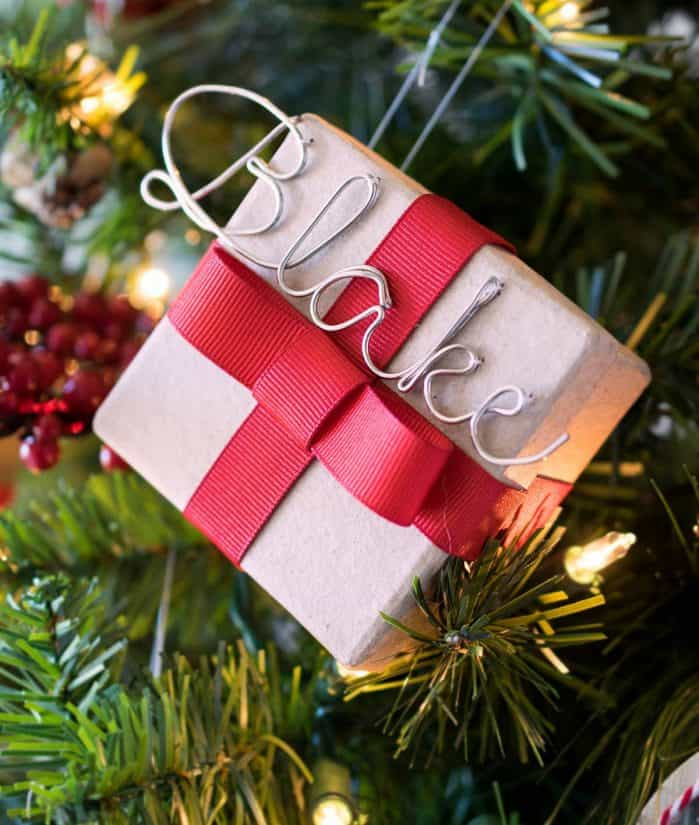 Small gift box with red ribbon and wire name as a Christmas tree ornament.