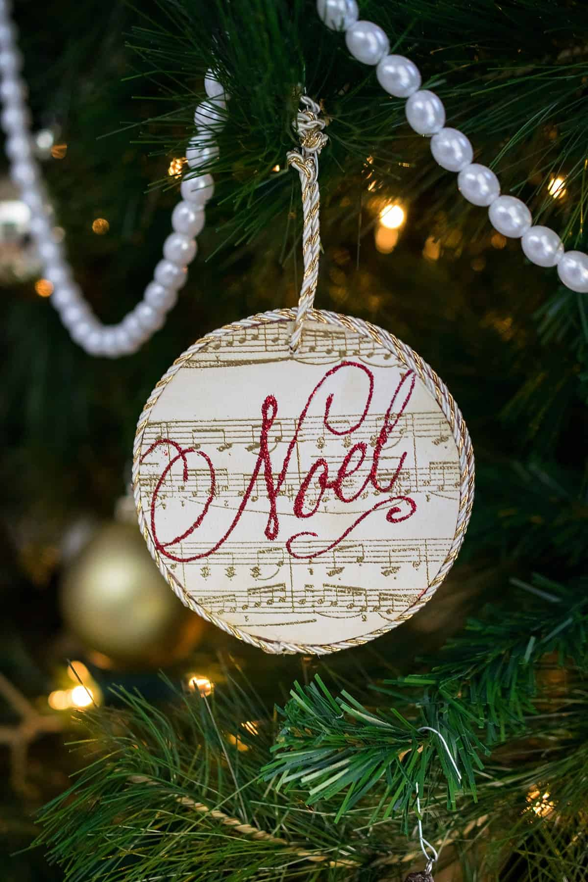 DIY round stamped ornament with gold sheet music print and Noel stamped in red lettering hanging from tree with beaded garland.