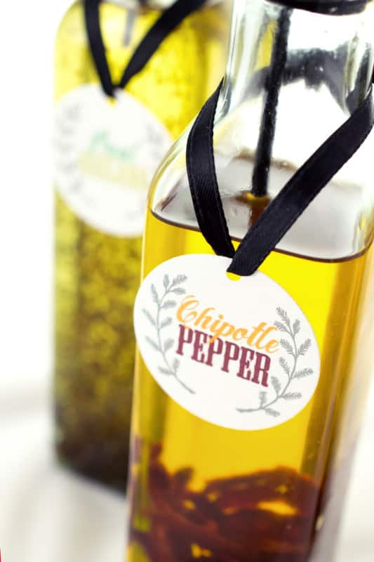 Closeup of printed chipotle pepper label tide to bottle of infused oil with black ribbon with basil oregano oil in background.