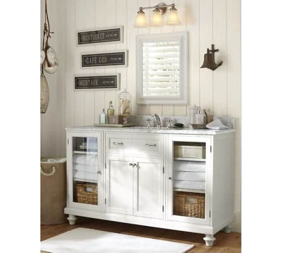 White vanity cabinet with glass doors filled with linens and baskets below white framed mirror and light fixture against white paneled wall.