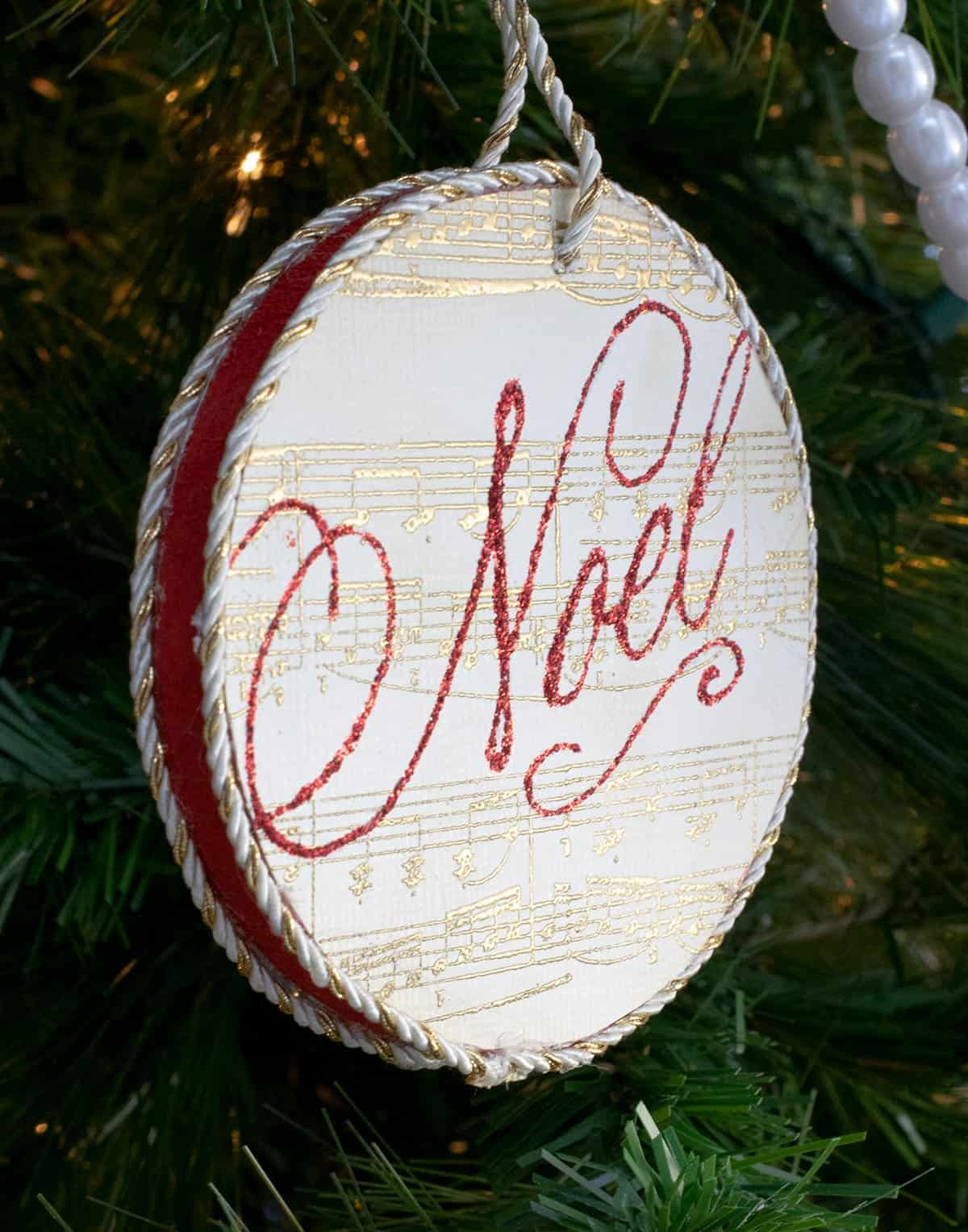 DIY round stamped ornament with gold sheet music print and Noel stamped in red lettering hanging from tree with gold rope.