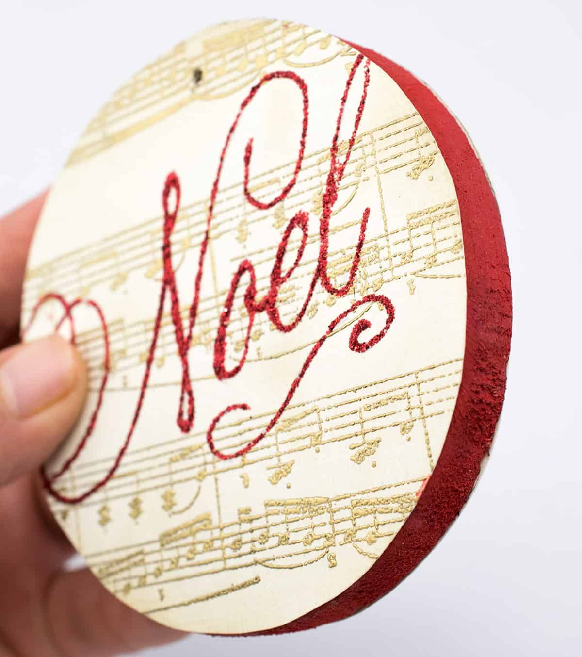 DIY stamped ornament on wood disk with gold sheet music and red glitter noel image with red painted sides.
