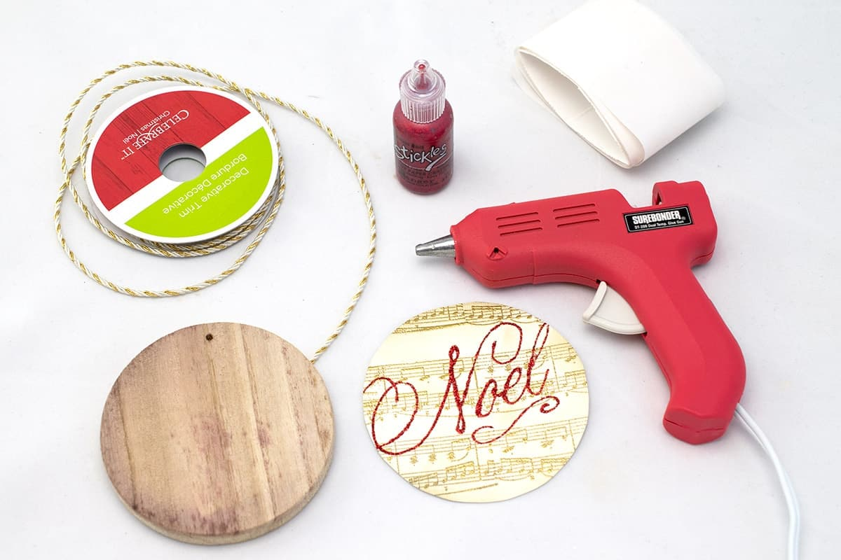 Supplies for making DIY stamped ornament-wood disk, stamped cardstock, glitter glue, glue gun, and hanging rope.