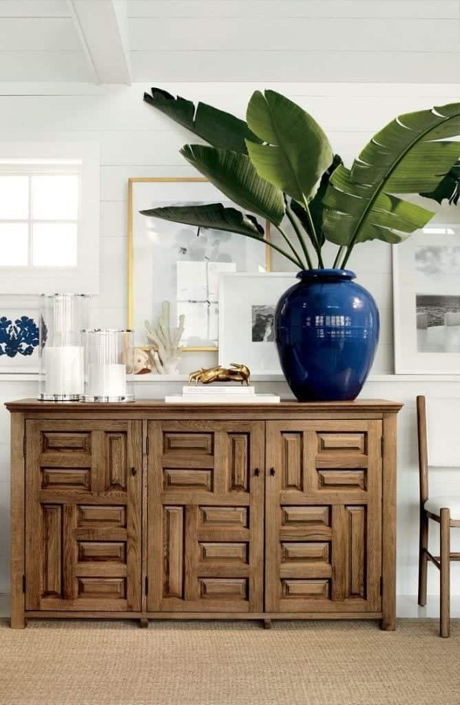 Geometric wooden credenza with large plant in blue ceramic pot, white candles in glass vessels in front of white paneled wall with framed pictures.