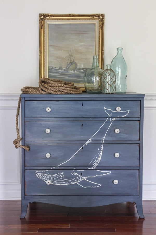 Chest of drawers with navy blue chalk paint finish with white whale image painted on front, topped with framed painting, and glass bottles.