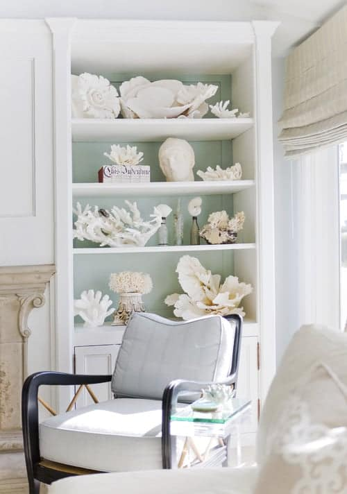 Large white Shelf with collection of white coral with soft green background with gray chair in front.