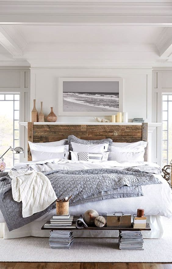 Neutral coastal bedroom decor with large wooden bed. white with gray and wood accents, black and white framed beach photo above bed.
