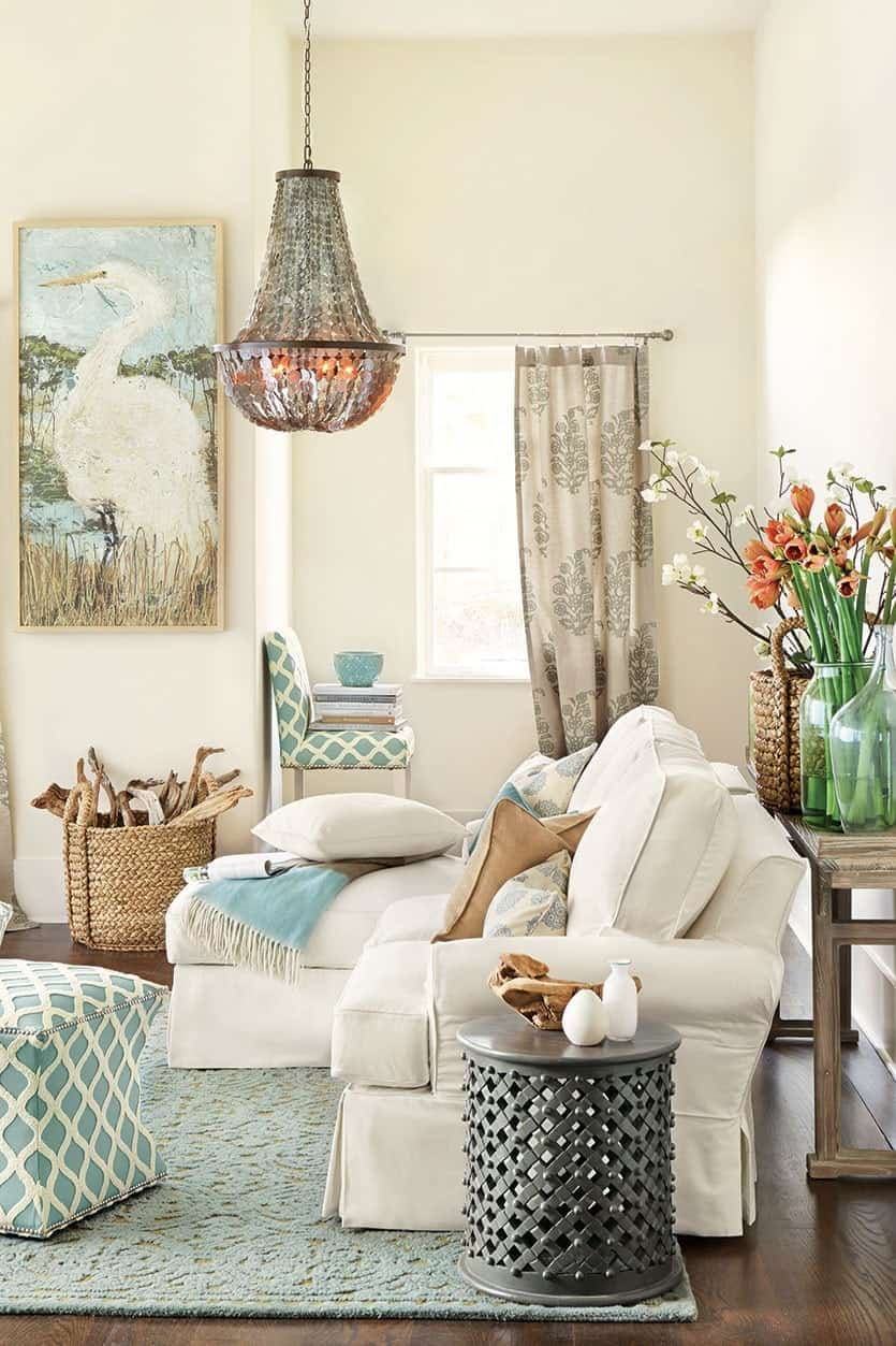 Beige sofa on soft green rug in living room with jewel chandelier, green chair and footstool, metal side table, flowers, and pelican painting.