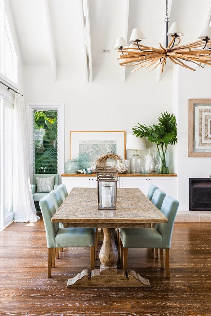 Dining room with white walls and white vaulted ceiling with wood dining table and teal upholstered chairs, topped with lanterns. Cabinets topped with framed picture, plant, and glass vases.