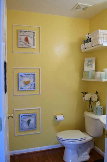 Before bathroom makeover with satin yellow walls and simple bird artwork