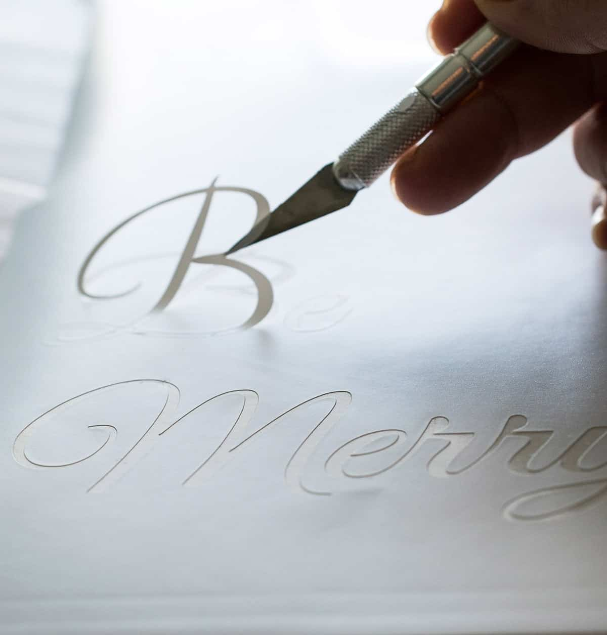 White sheet with Be Merry message stencil being cut out with metal crafting knife.