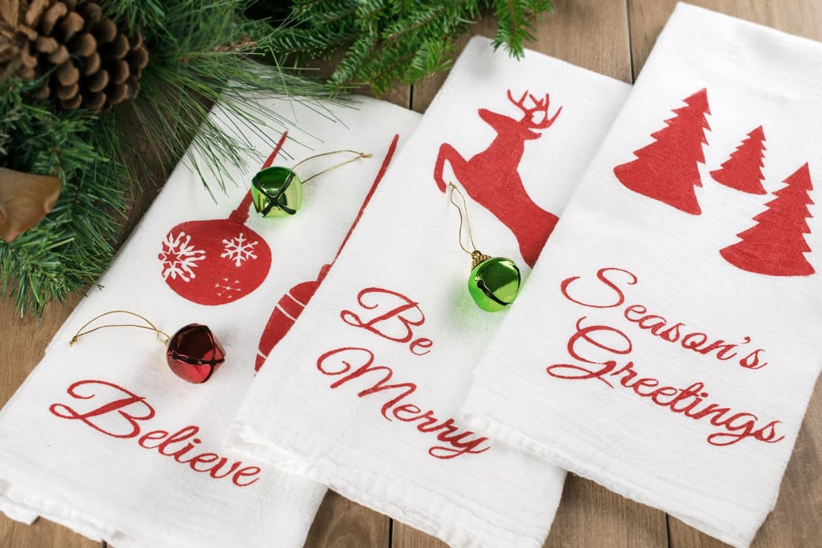 Three white tea towels with red Christmas themed stencils spread on wooden surface with garland, pine cones, and ornaments.