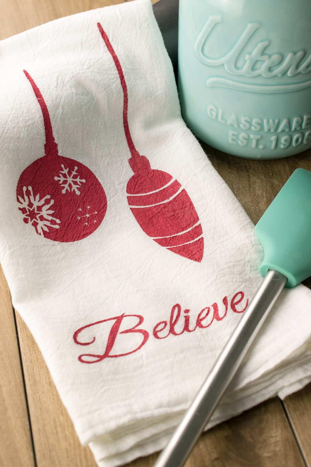 White tea towel with ornaments and Believe message stencil with teal spatula and canister on wood surface.