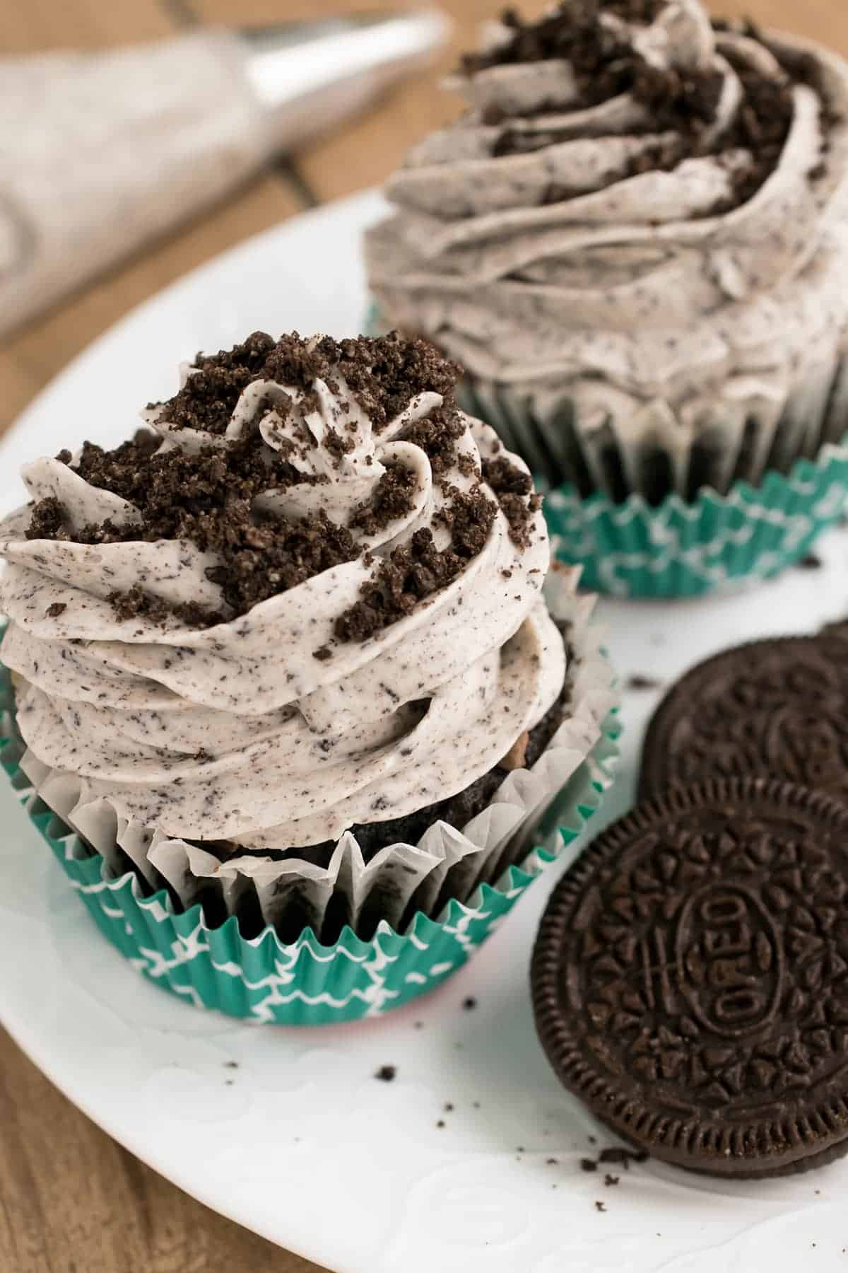 Two chocolate cupcakes in turquoise liners on white plate next to stacked Oreo cookie.