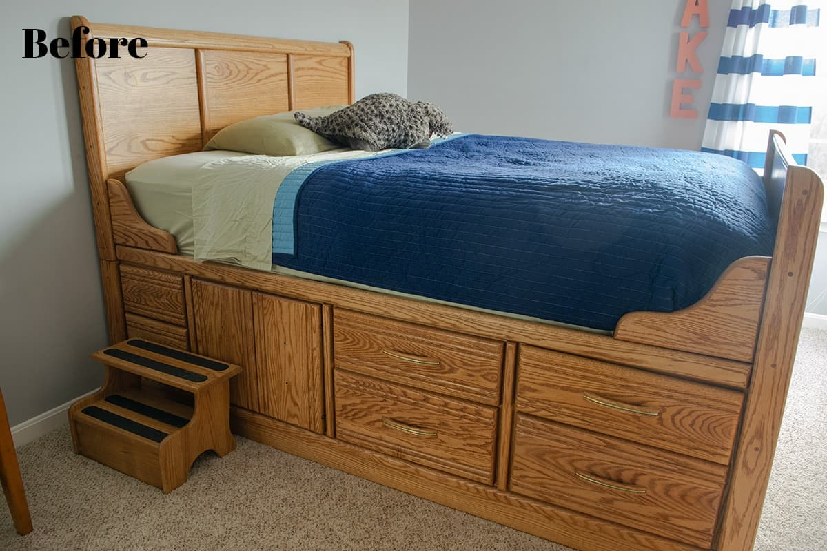 Wood captain's bed with step stool with navy blue comforter in little boy's room