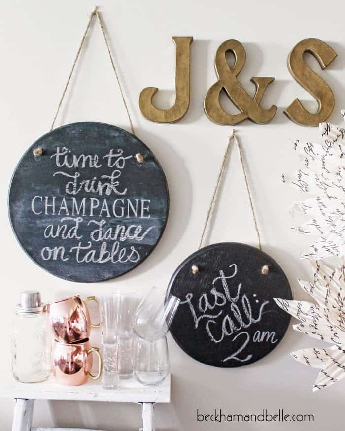 Round hanging chalkboard art above white side table with assorted glasses and bronze letter art.