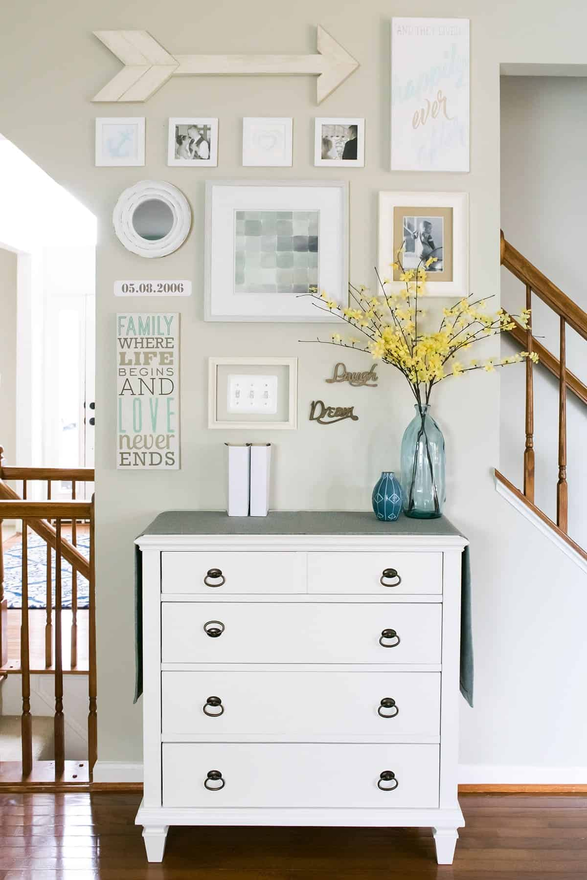 Easy watercolors and pencil drawings are used to create this personalized happily ever after gallery wall in the living room. The layout incorporates an awkward outlet and lots of DIY Art.