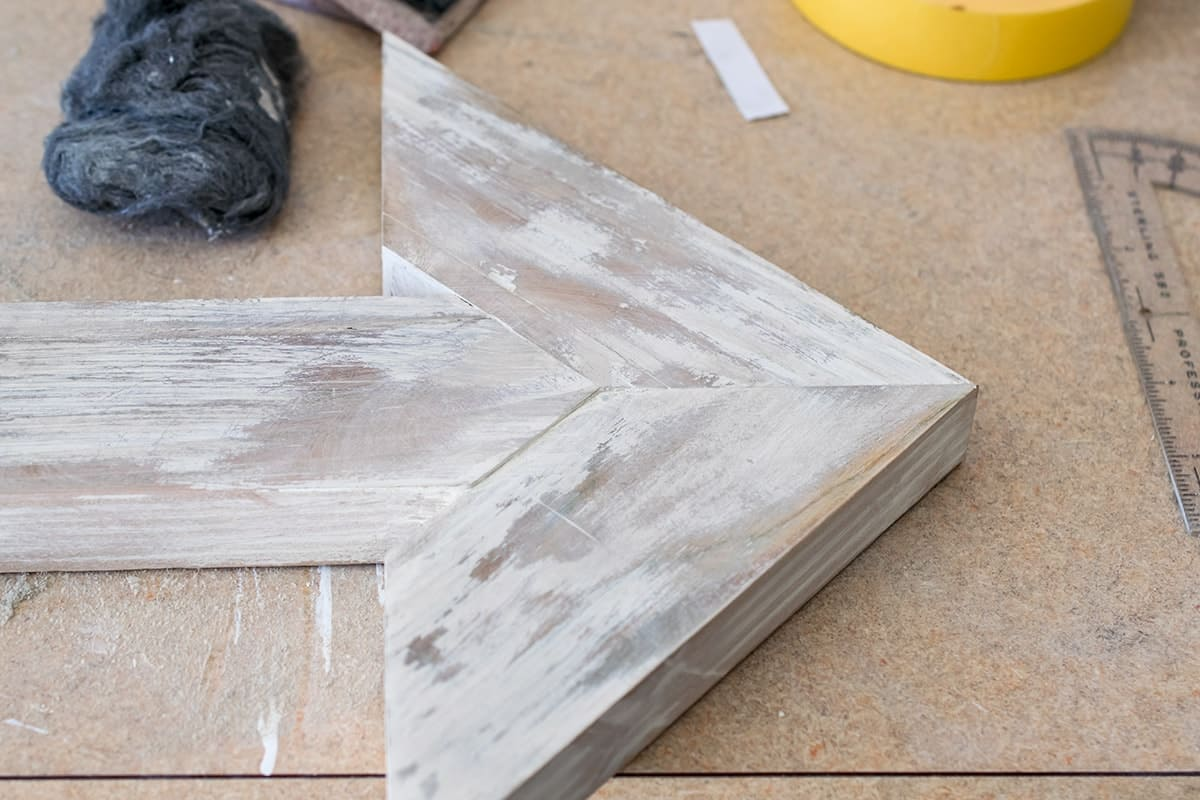 Whitewash finish on DIY wooden arrow point laying on work bench next to tools.