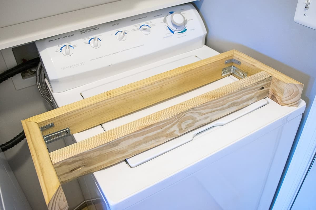 A wood frame from above that is used for attaching trim with L-brackets and a corner brace.