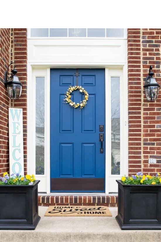 Add more curb appeal to your house -- and increase its value -- with these easy exterior improvements. Welcome spring in all its glory with a themed wreath or paint the door a bold and contrasting color such as this blue door against the red brick house. Some seasonal flowers and a welcome sign pull the updated look together and welcome visitors to your home.