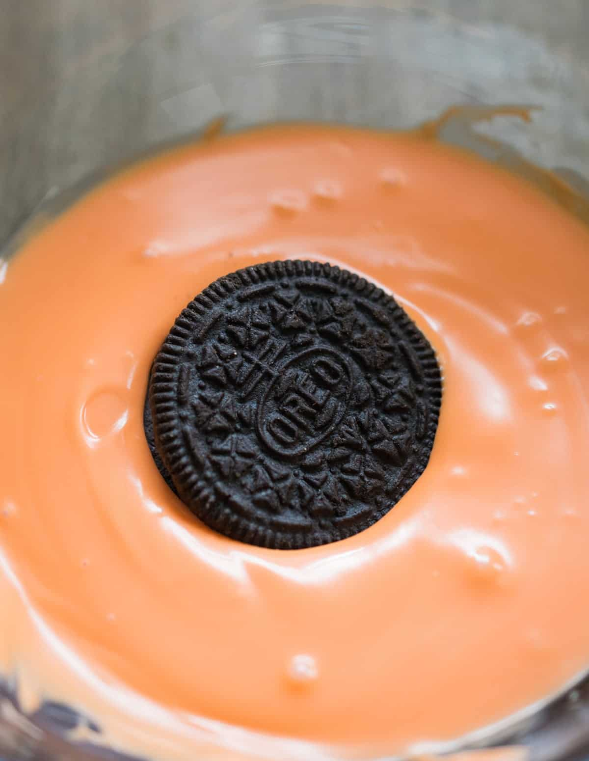 Oreo in orange tinted white chocolate in glass bowl for making basketball cookies.