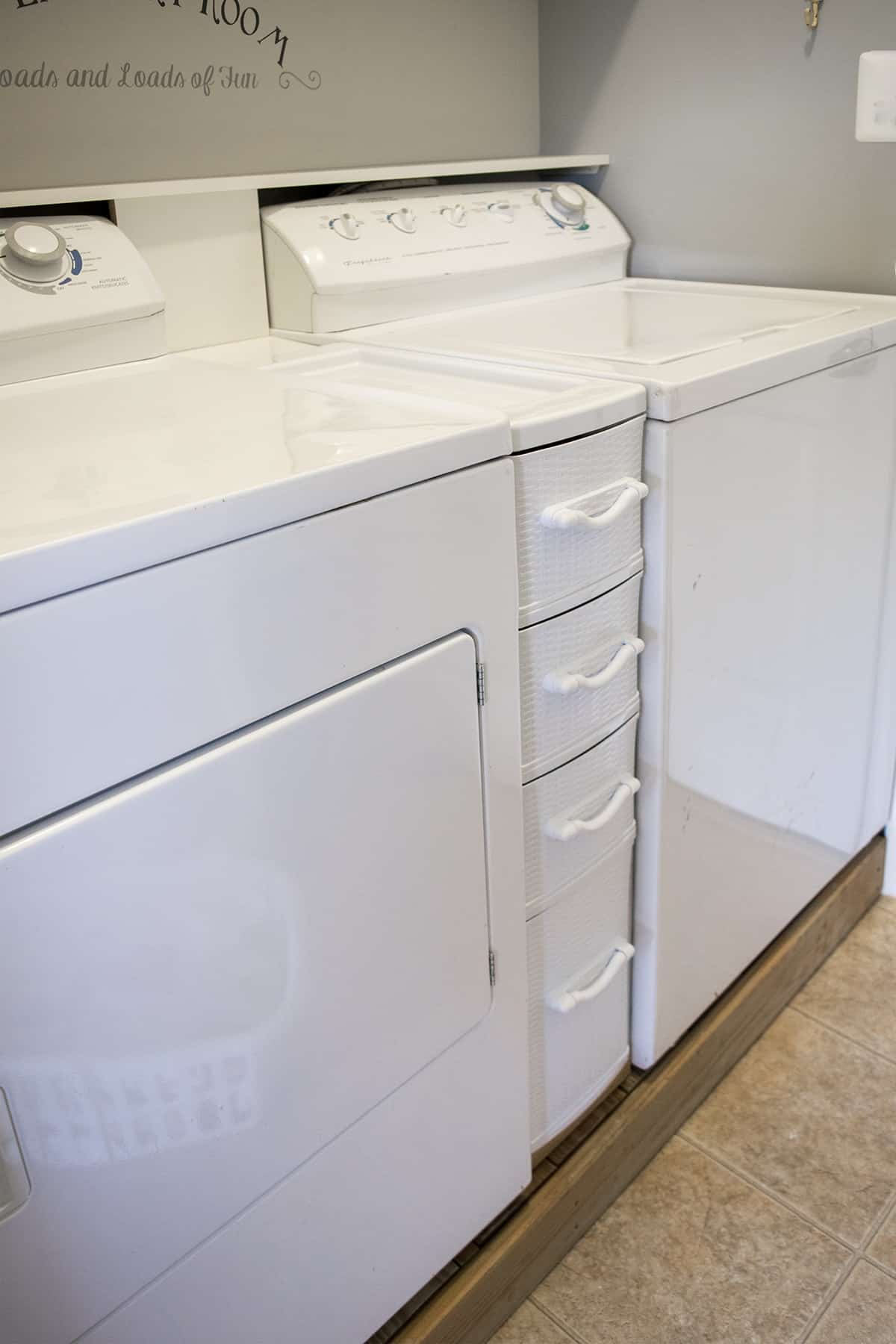 Washer and Dryer on a Platform for easier reach with storage console between them. How to easily organize laundry supplies and rags.