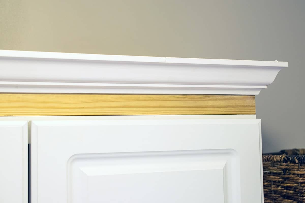 Corner of top of white cabinet with framing piece and crown molding attached.