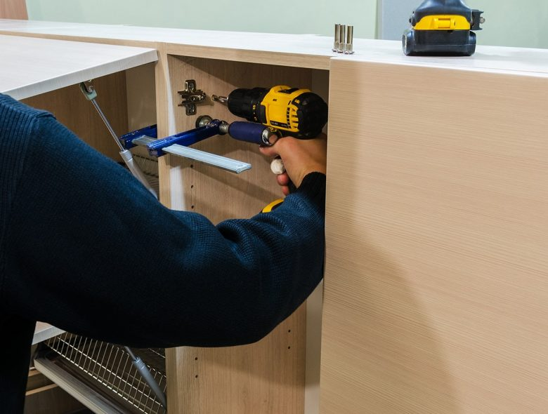 Man using a drill and clamps to attach wall cabinets together