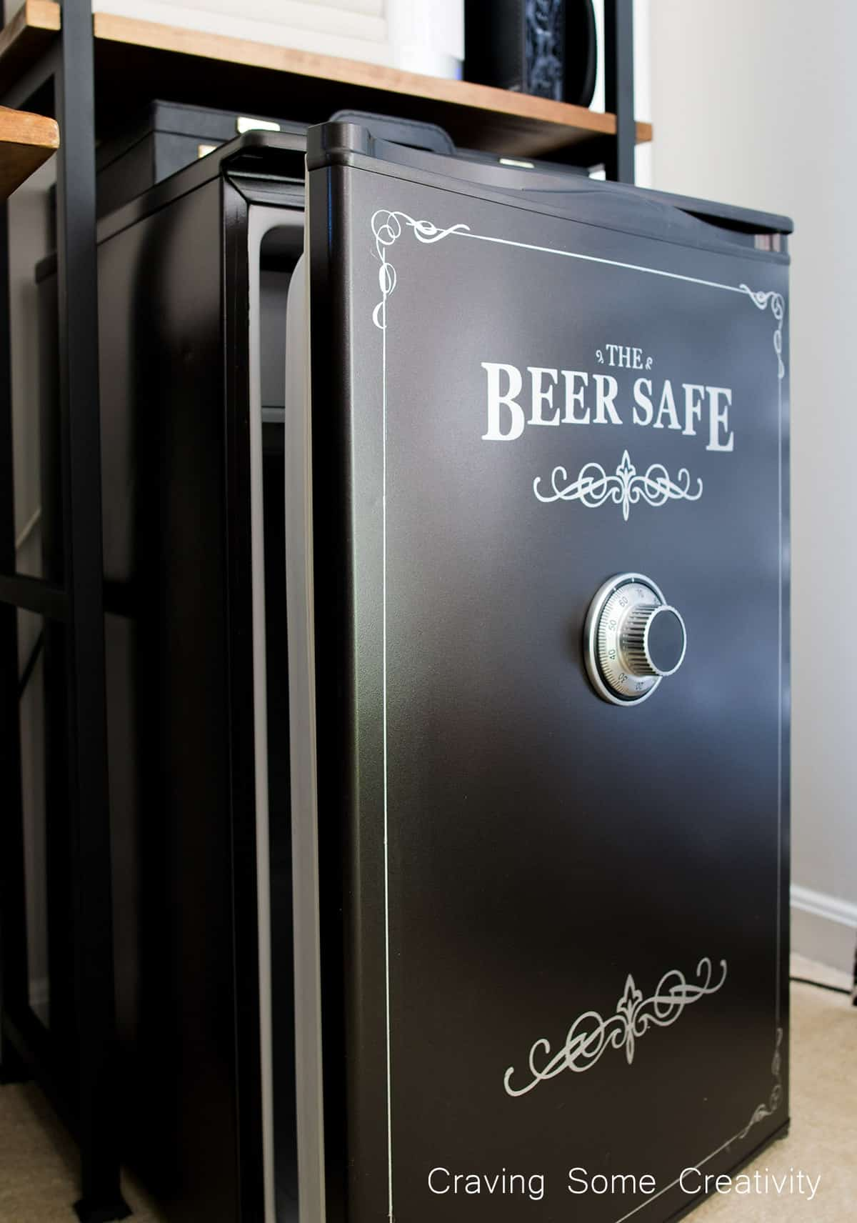 Completed black mini refrigerator makeover with vinyl beer safe stencil and safe dial.
