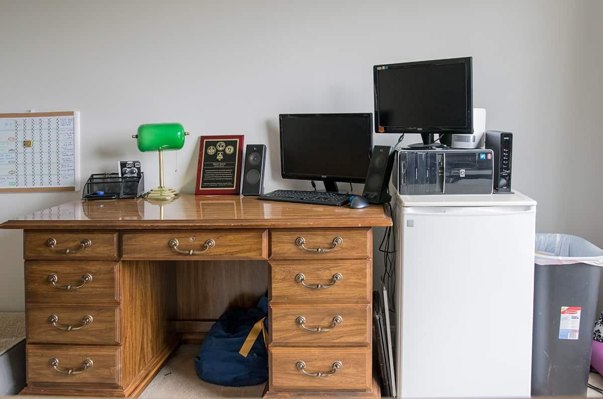 Antique desk in cluttered office before makeover.