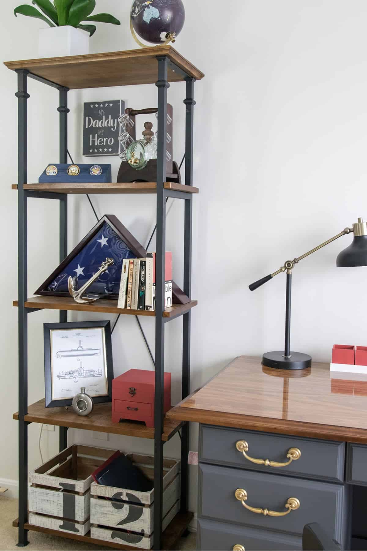 Industrial looking wood and black metal office shelf with patriotic pictures and decor next to desk.
