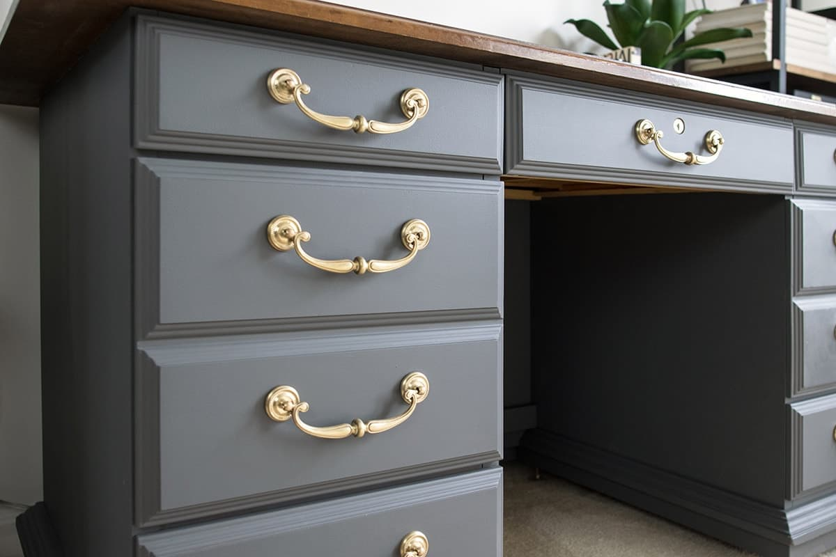 Grey Desk with Brass Hardware and a wood top. This antique painted desk update used gray chalk paint to create a regal style.