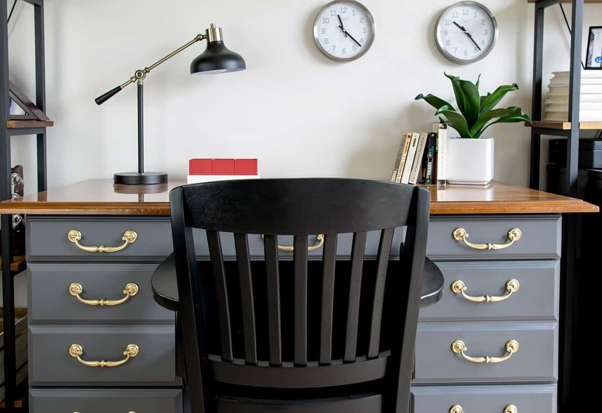 Black office chair in front of gray vintage desk with brass hardware after makeover.