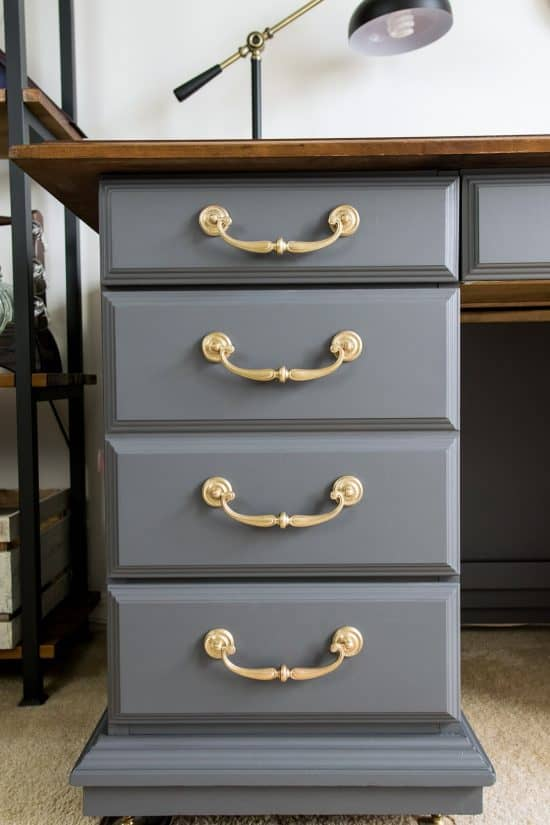 Gray painted desk with brass handles and a wood top.