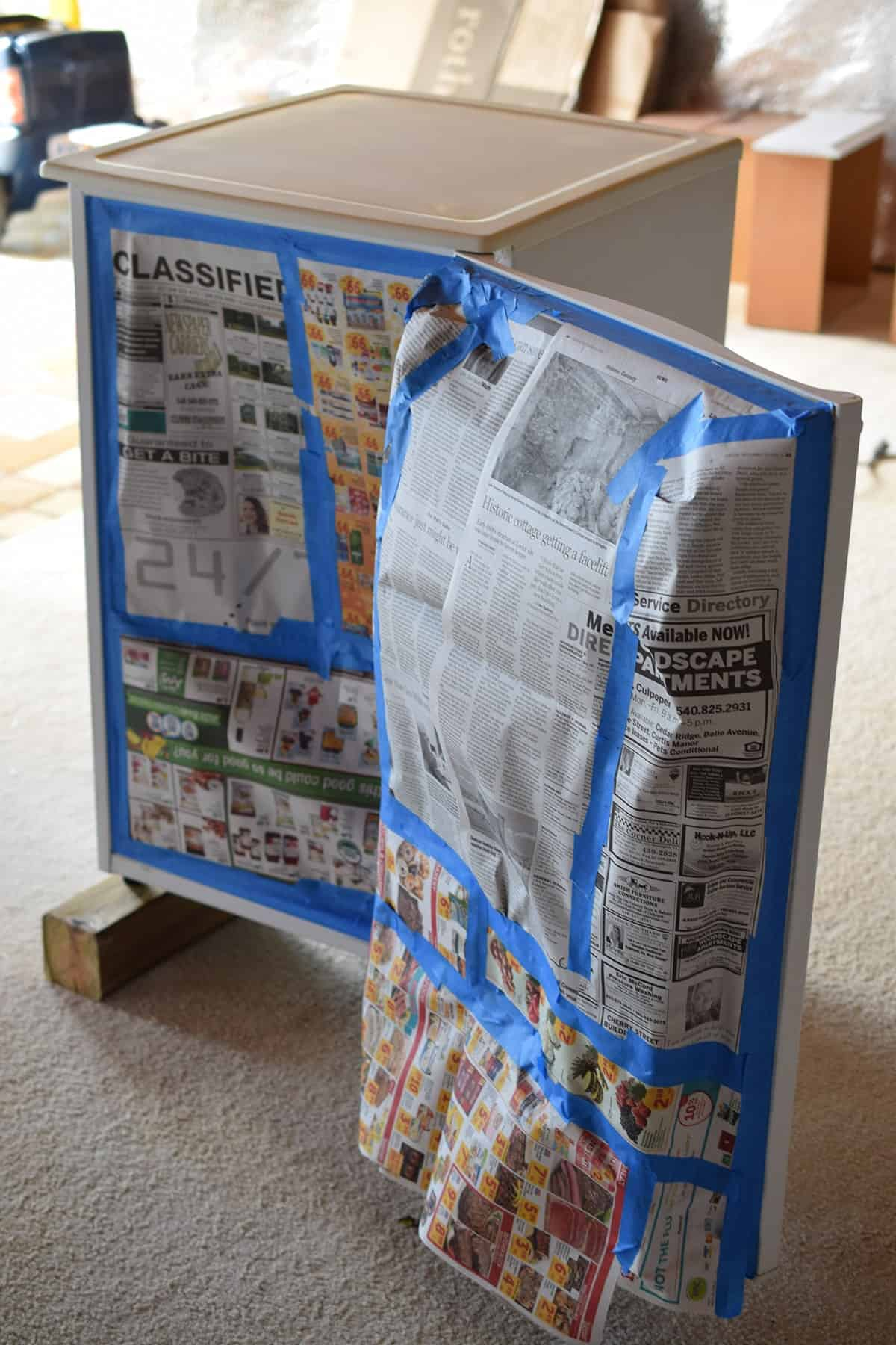 White mini fridge on wooden blocks, taped with newspaper in preparation for painting.