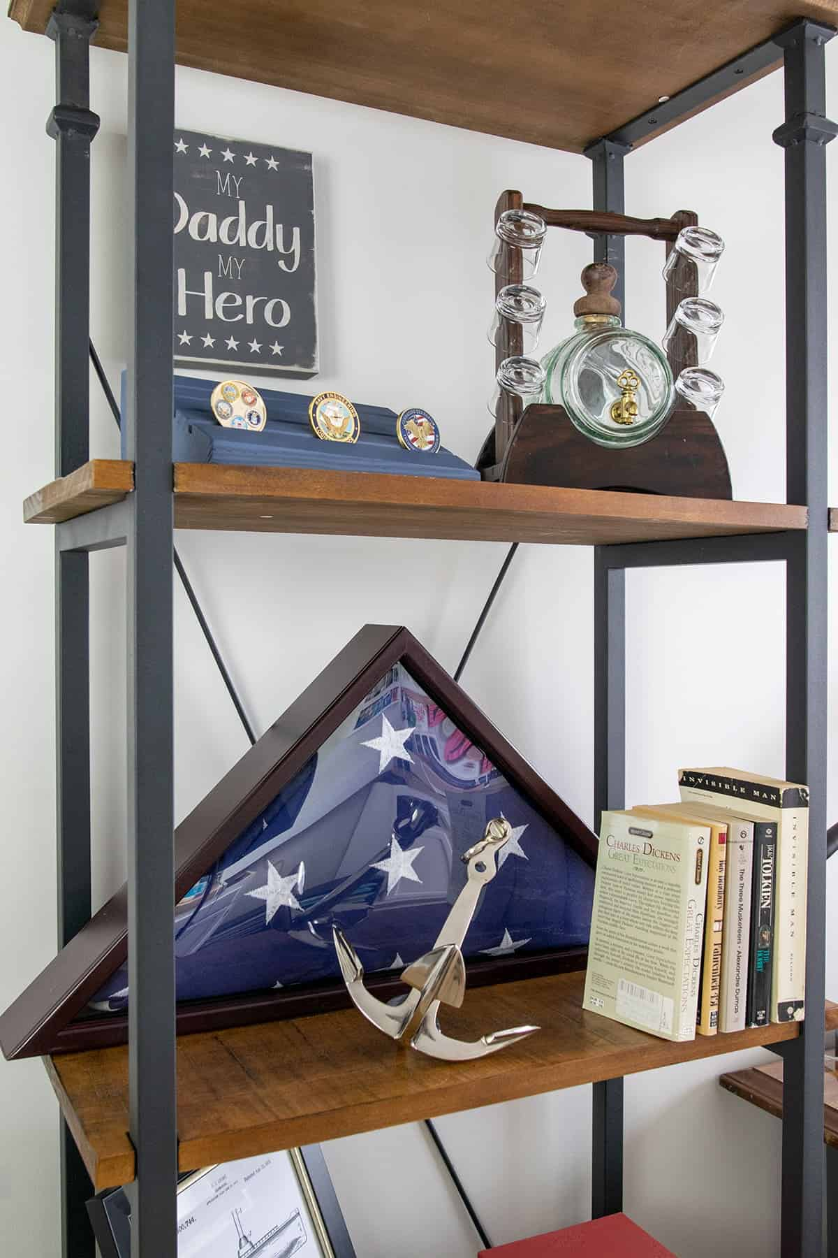 Industrial looking wood and black metal office shelf with patriotic decor and books.