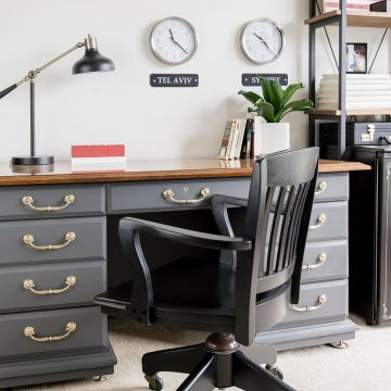 Masculine gray office with antique desk and black office chair. World clocks on the wall.