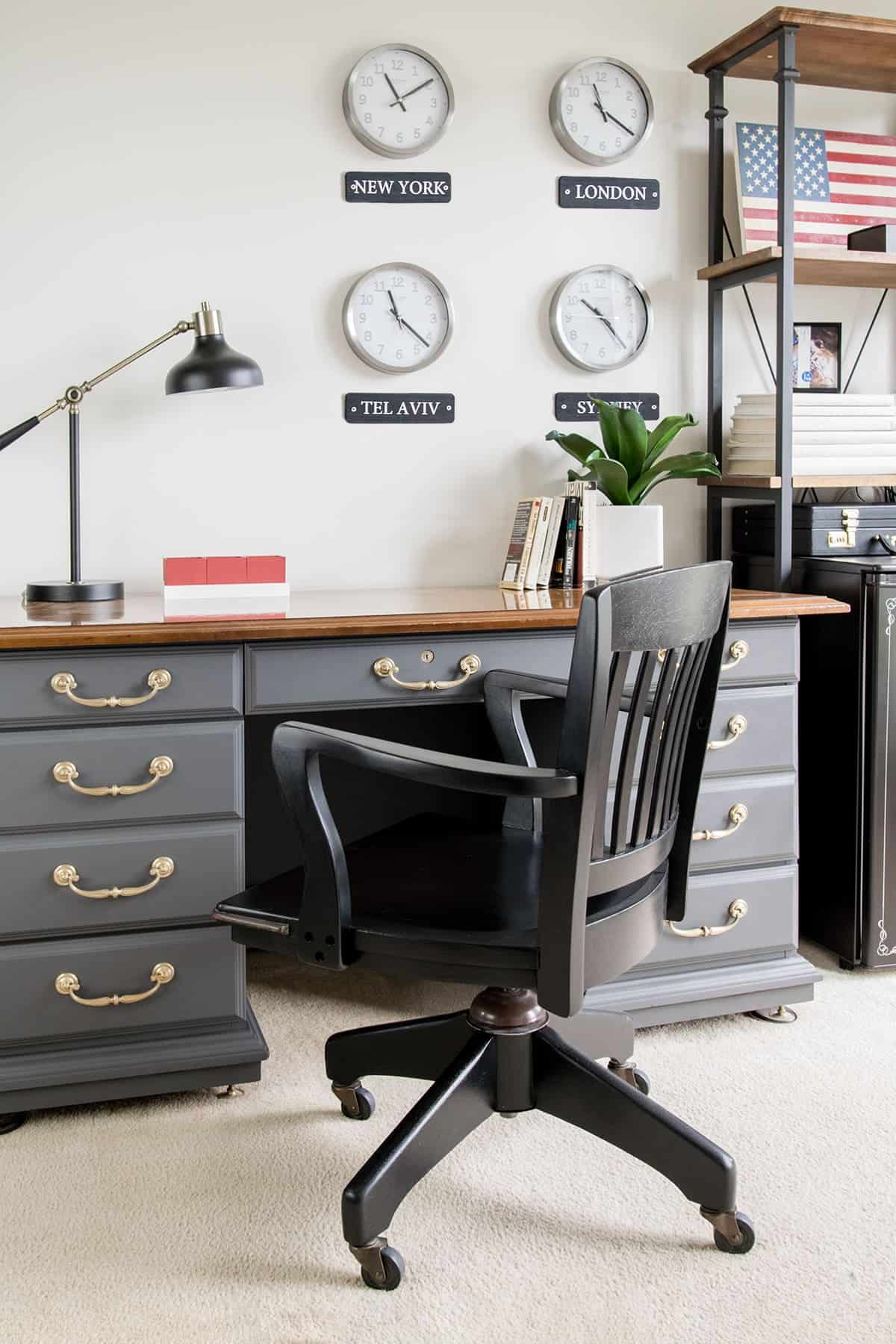 Masculine and patriotic home office after makeover with world clock display, refinished antique desk, and painted office chair.