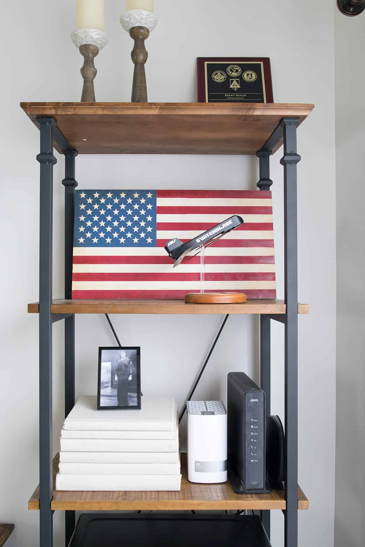 Industrial looking wood and black metal office shelf with patriotic pictures and decor.