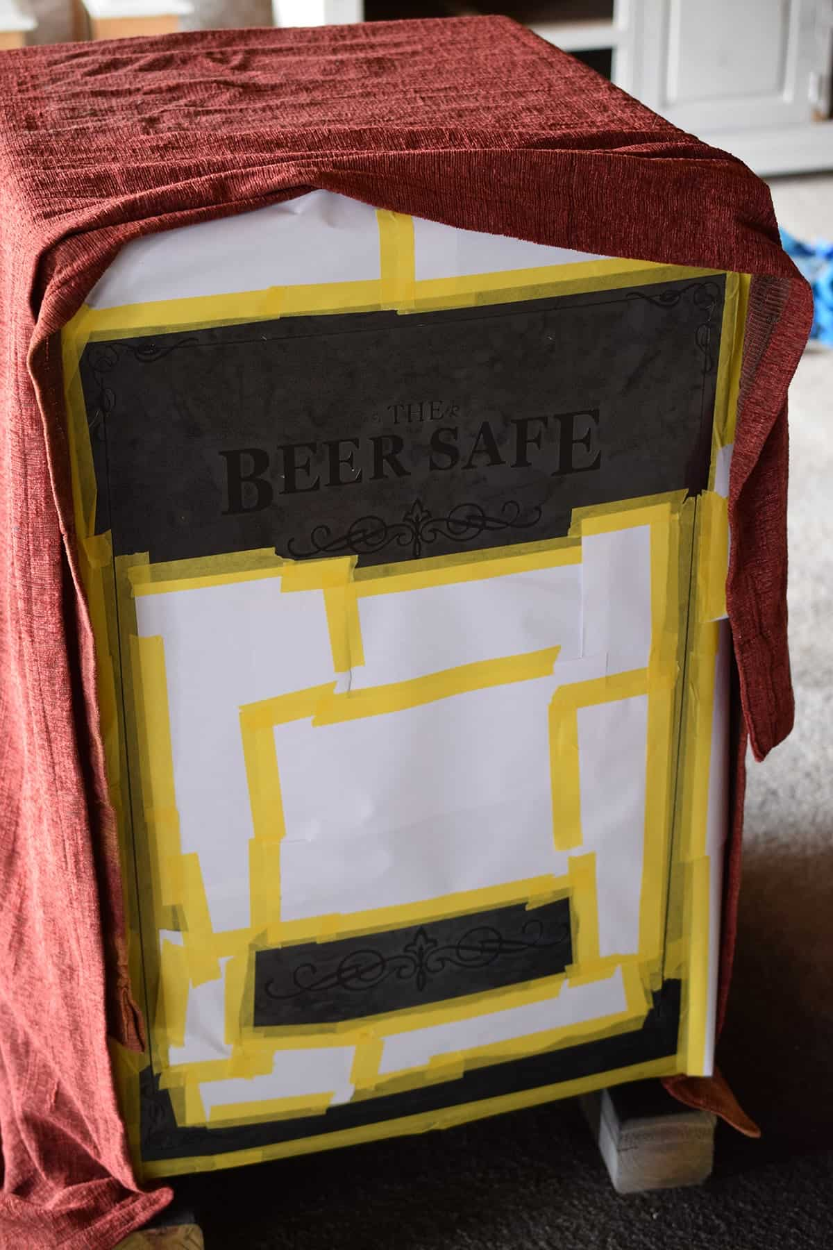 Mini fridge underneath red cloth with front door taped off in yellow tape and beer safe stencil applied.