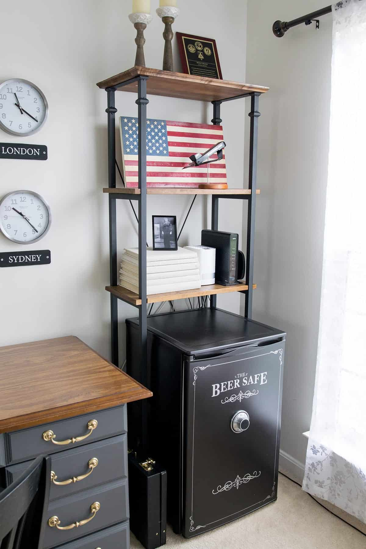 Industrial looking wood and black metal office shelf with patriotic pictures and decor with safe inspired mini fridge underneath
