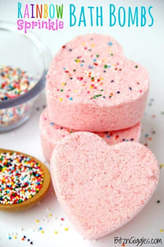 DIY pink sprinkled bath bombs in heart shapes next to bowl of rainbow colored sprinkles.