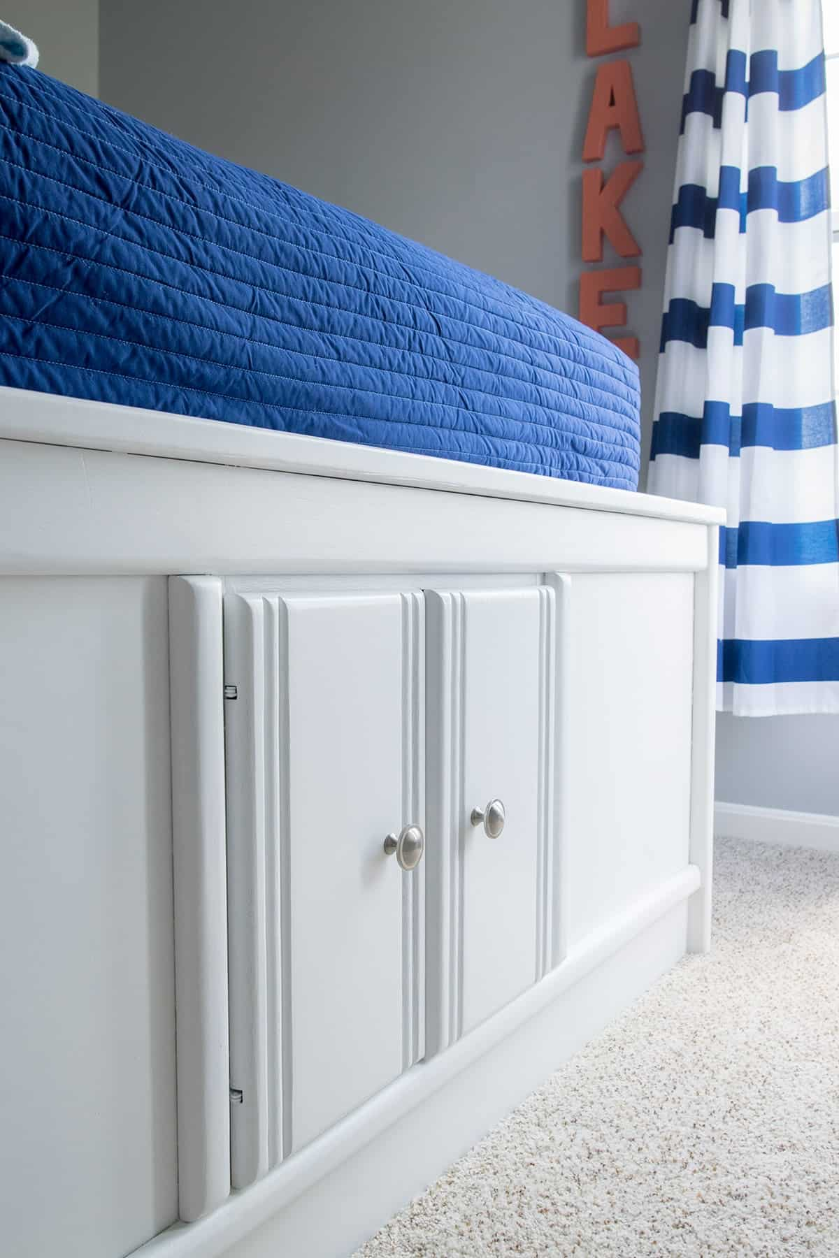Captain's bed with cabinet storage in fresh white finish with satin nickel hardware.