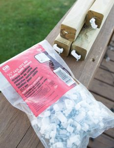 Bag of plastic cable staples on top of wooden handrail on outdoor deck