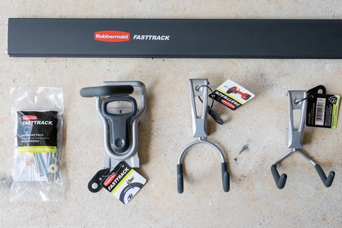 Rubbermaid Fasttrack rail and wall hooks laying on concrete.