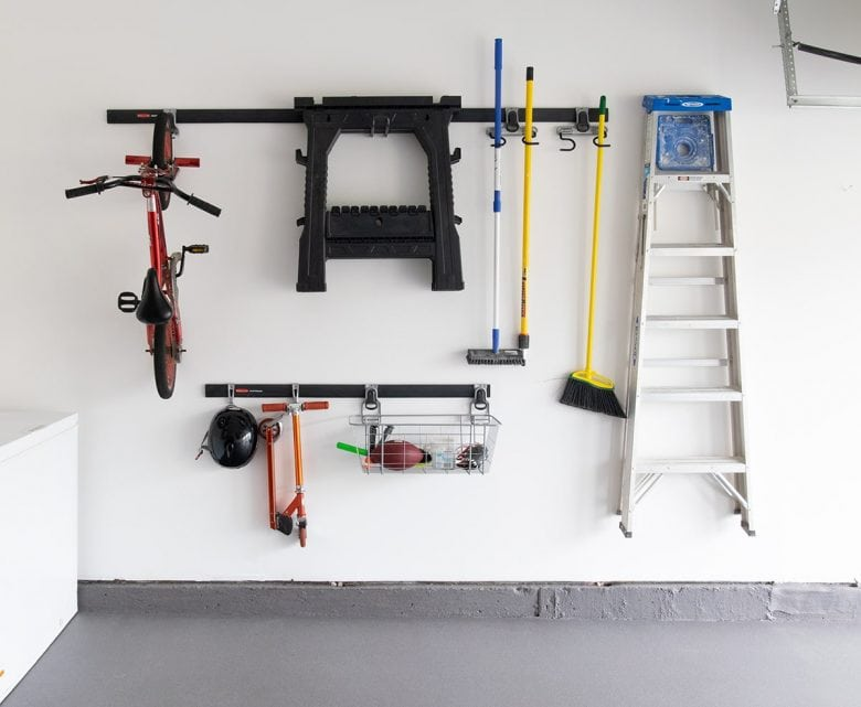 An organized garage wall with tools and toys on hanging hooks.