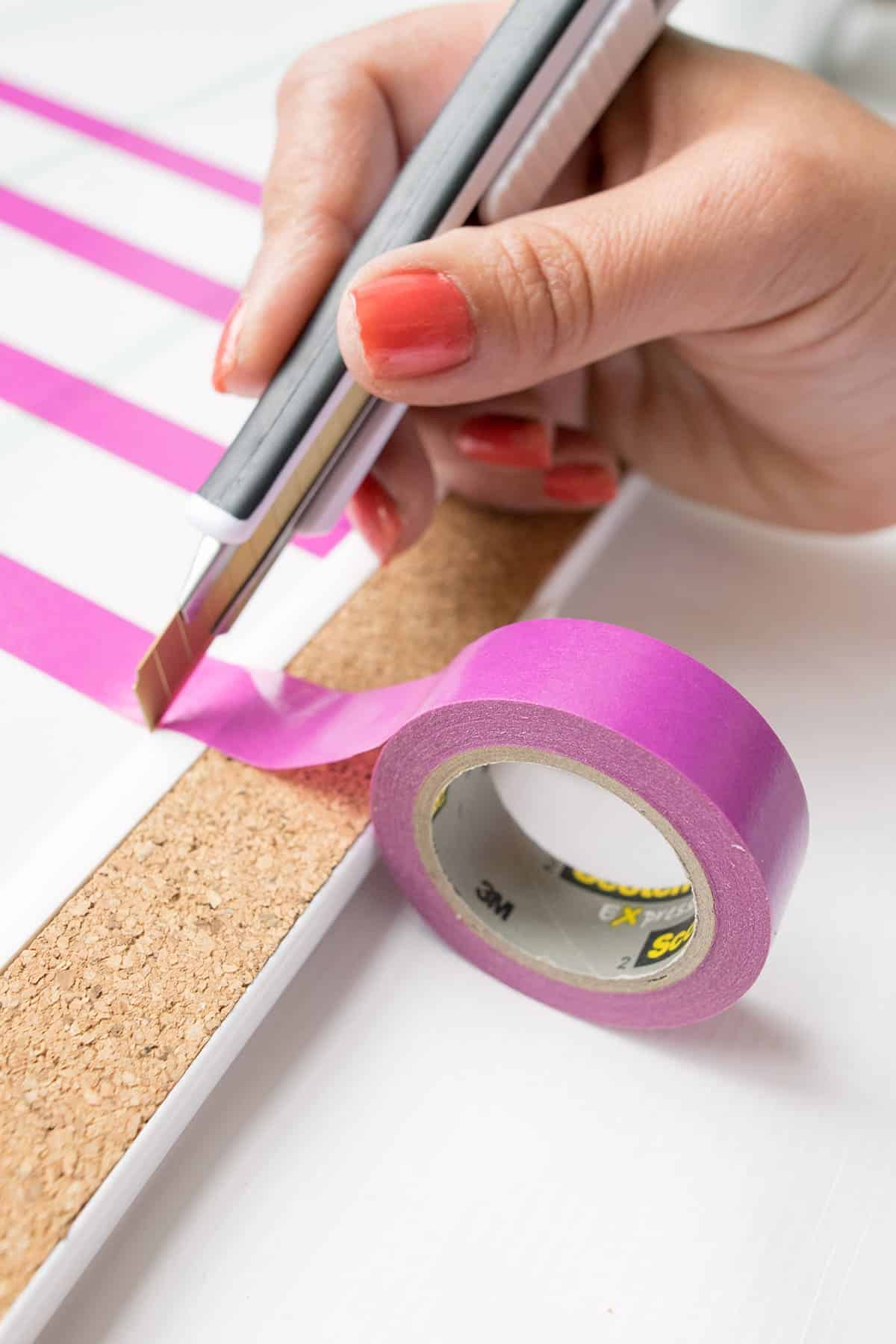 Pink double sided tape applied to dry erase board for DIY weekly chore chart.