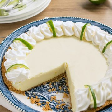Key lime pie on blue plate with a slice cut out to show texture.